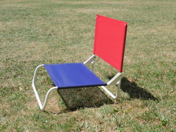 Chaise de plage la chaise française bleu et rouge_ L'Inatelier Nantes Design et artisanat francais en situation de profil sur gazon